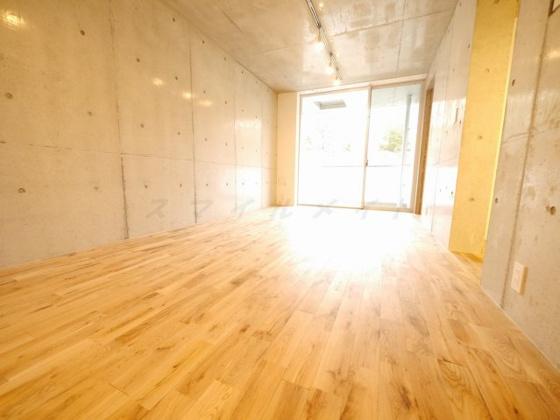 居間木の風合いがお洒落なフローリングにコンクリート打放のリビング